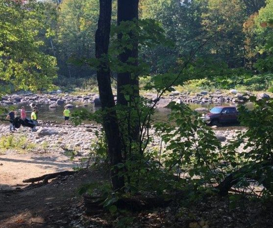 Games wardens and sheriff's deputies investigate a Chevrolet pickup truck that was abandoned Sunday morning in the Carrabassett River in New Portland. The truck's owner was charged by police with leaving a submerged vehicle in a waterway.