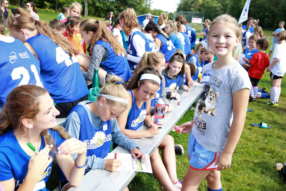 Lydia Parent, a third grader from Williams Elementary School in Oakland, gets autographs from first in line Maya Chalmers, Amelia Bradfield, Caitlin Parks and other members of the Messalonskee High School Girls Soccer team during the second annual