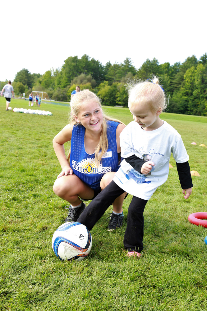 "Messalonskee Girls Soccer player Molly Calkins shares her soccer skills with 3-year-old Claire Slevinsky from South China at ""Shine On Saturday,"" a youth girls mentoring day established by Messalonskee Girls Soccer and the ShineOnCass Foundation in honor and memory of Cassidy Charette."
