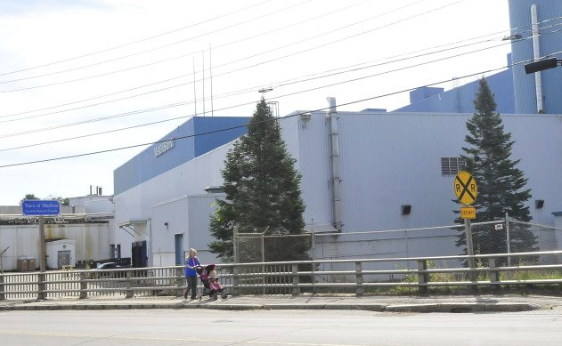 "A woman and baby walk past the front of the shuttered Madison Paper Industries mill near a town ""business friendly"" sign on Thursday. The town is suing the owners of the former mill for information regarding property values."