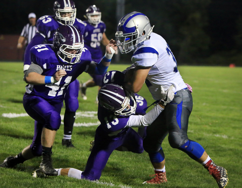 Marshwood's Ian Parmley tackles Lawrence ball carrier Tyler Larouche during a Class B game Friday night.