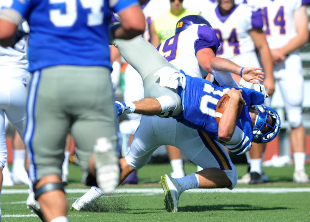 Colby College quarterback Jack O'Brien (10) gets hit  by Williams College's Jameson DeMarco (49) as runs for the first down Saturday at Colby College in Waterville.