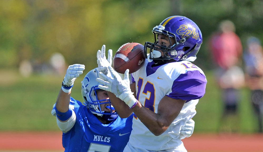 Williams College receiver Justin Nelson (13) makes a catch as Colby College's Patrick Yale (5) defends Saturday at Colby College in Waterville.
