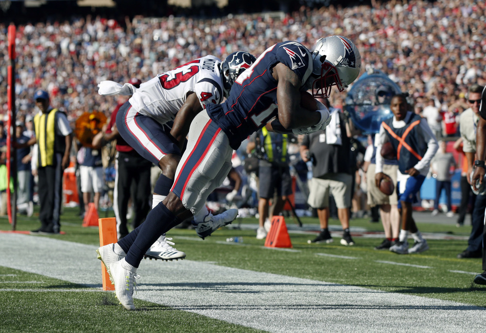 New England Patriots wide receiver Brandin Cooks, right, drags his toes as he makes the game-winning catch in the end zone for a touchdown in front of Houston Texans safety Corey Moore, left, during the second half Sunday in Foxborough, Massachusetts.