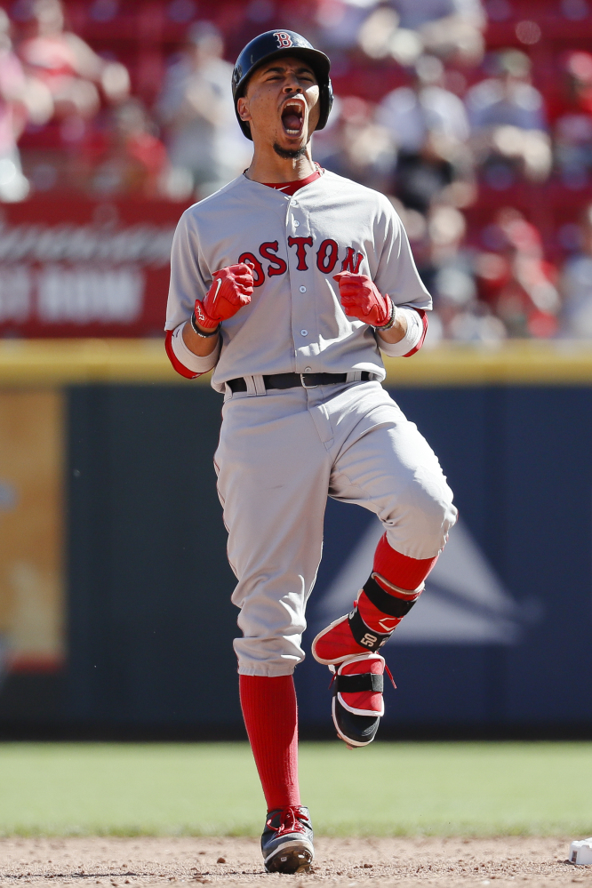 Boston's Mookie Betts reacts after hitting the game-tying three-run double off Cincinnati relief pitcher Raisel Iglesias on Sunday in Cincinnati.