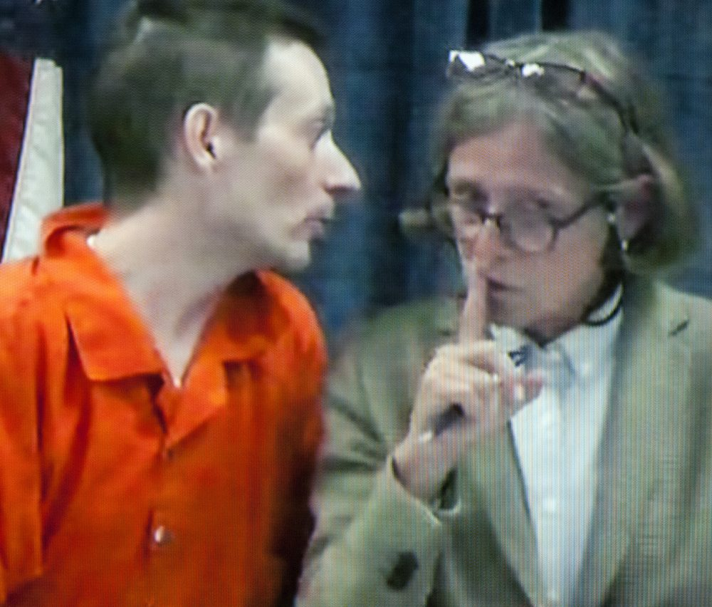 Attorney Lisa Whittier, right puts her finger to lips to signal Scott Bubar to stop speaking as they appear in court via video from Kennebec County jail on May 30 at the Capital Judicial Center in Augusta.