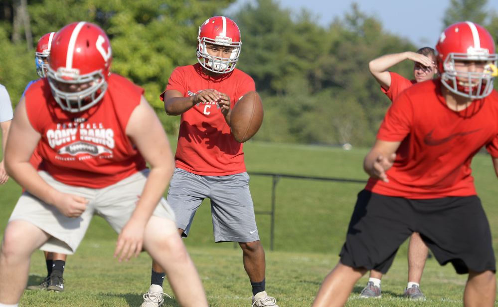 Members of the Cony football team run a drill during practice Monday at the Augusta school.