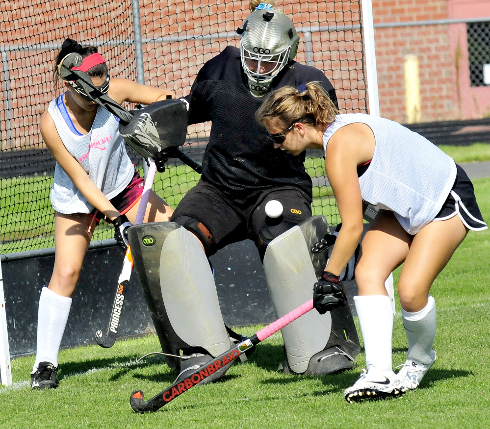 Skowhegan field hockey goalie Leah Savage makes a save as sweeper Haley Carter, left, and Elizabeth York apply pressure during an August practice in Skowhegan.