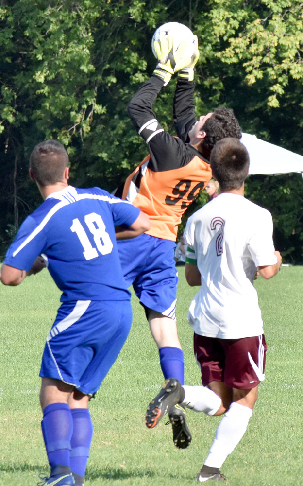 Mountain Valley goalie Jacob Rainey makes a leaping grab while teammate Garrett Garbarini and Monmouth's Avery Pomerleau look on during a Mountain Valley Conference game Tuesday in Monmouth.
