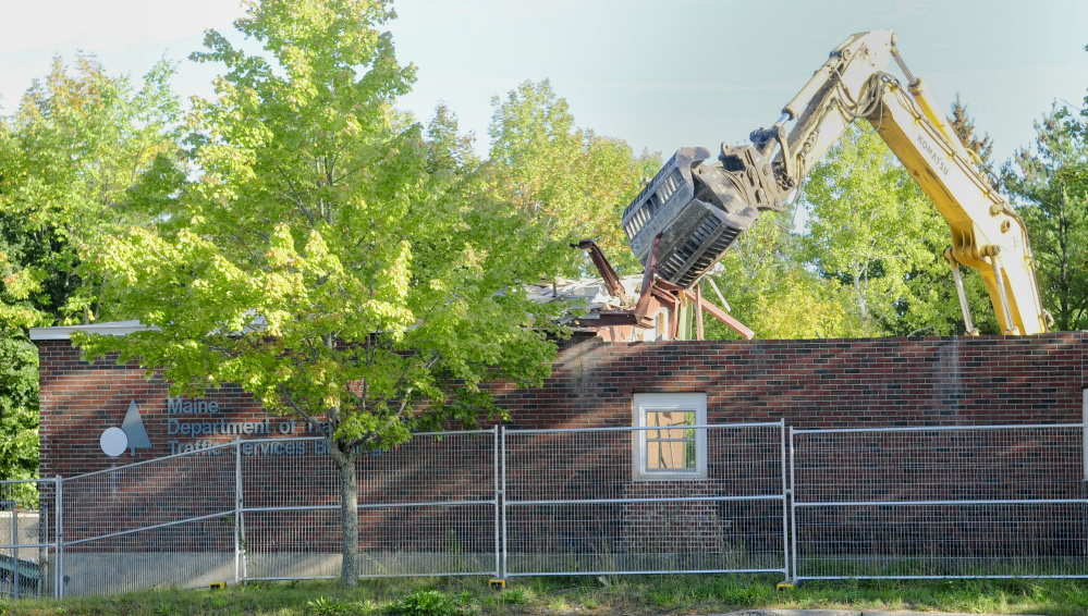 An excavator with a claw rips apart an old Department of Transportation building Friday in Augusta, where developers plan to build two new office buildings and lease space back to the state on Capitol Street.