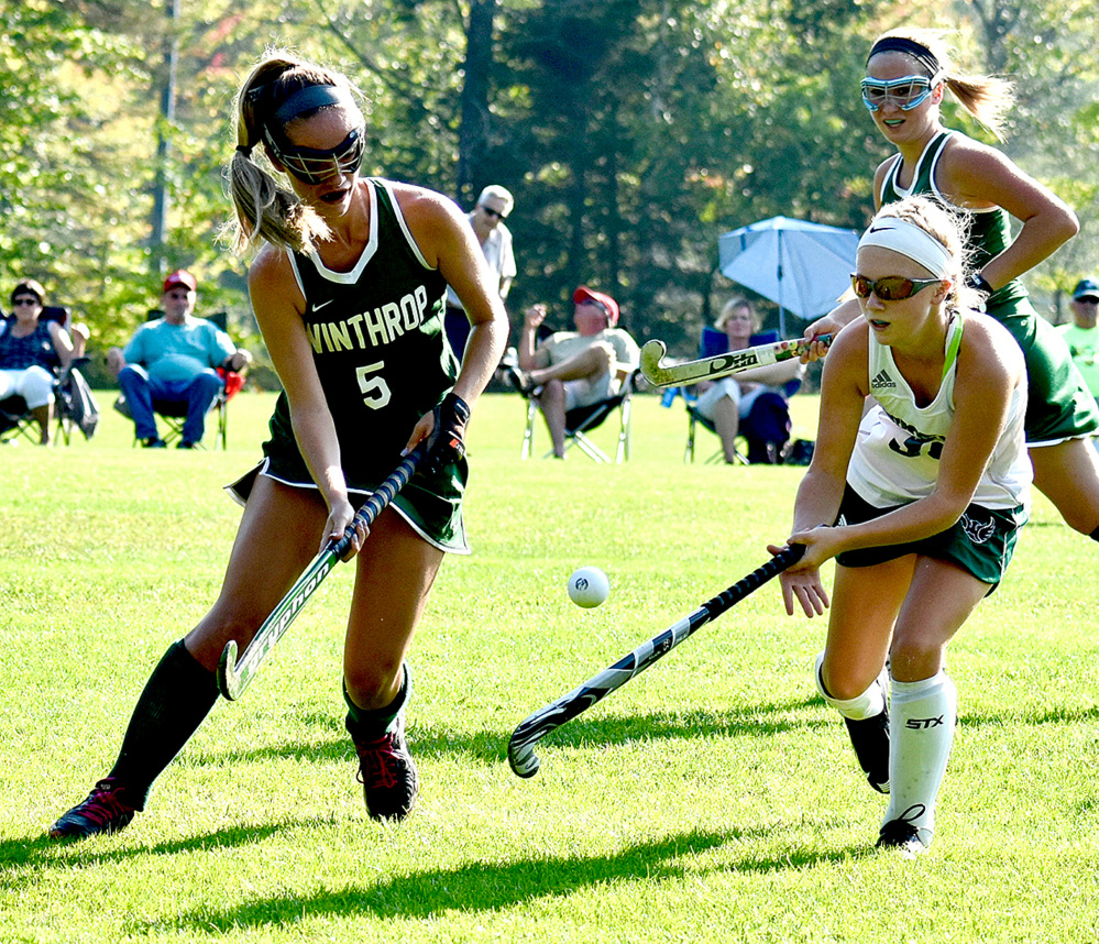 Winthrop's Olivia Simonson and Spruce Mountain's Emily Castonguay battle for the ball in a field hockey game in Jay on Wednesday,