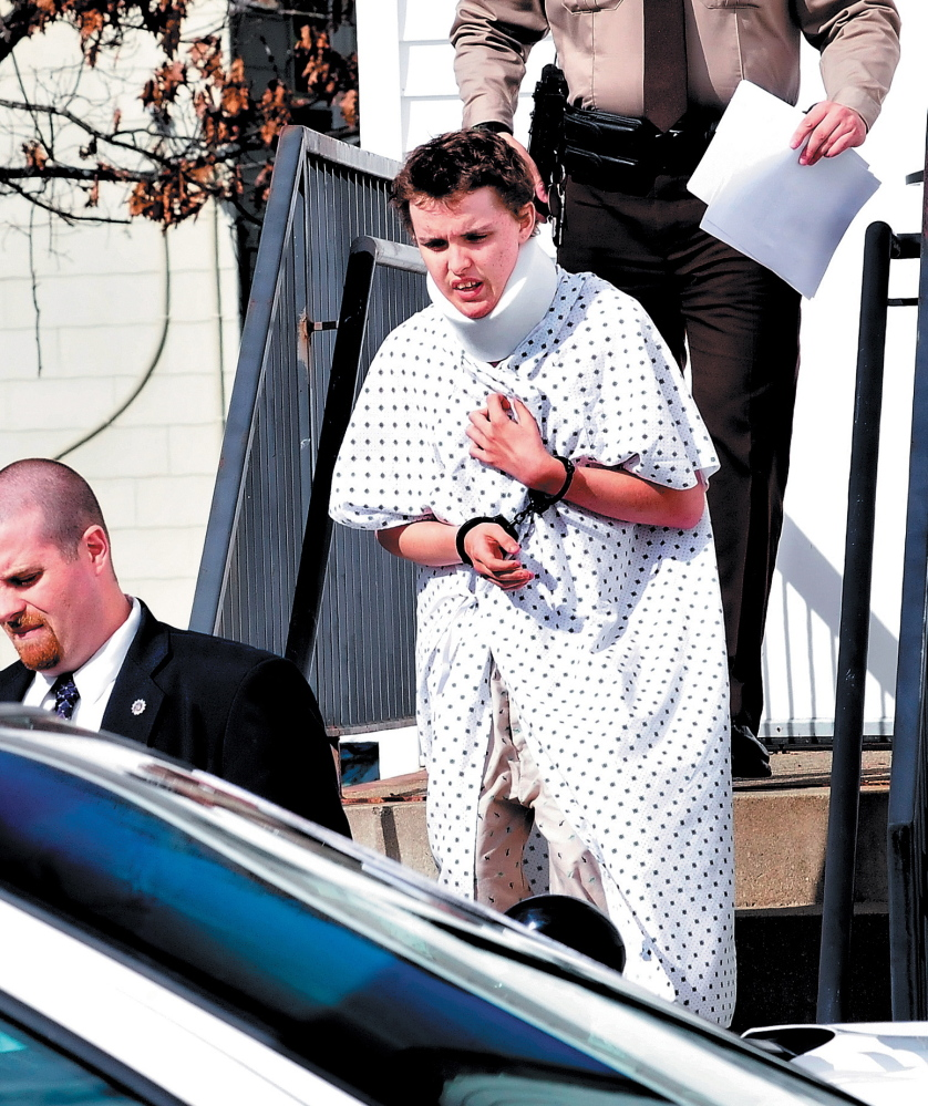 Wearing a hospital gown and neck brace from injuries suffered in a car crash, Zachary Wittke exits the Franklin County District Court in Farmington on Oct. 15, 2013, after a hearing on charges of eluding police, passing a roadblock and aggravated criminal mischief.