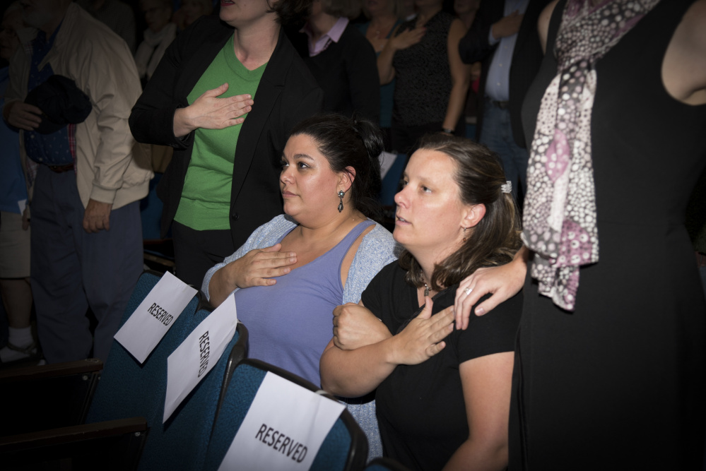 April Fournier, left, of Portland, and Liz Smith, of Camden, kneel while reciting the Pledge of Allegiance during the opening of a Democratic gubernatorial candidates' forum held Thursday evening at the University of Maine at Augusta. Zak Ringelstein led the Pledge of Allegiance and invited attendees to stand or kneel.