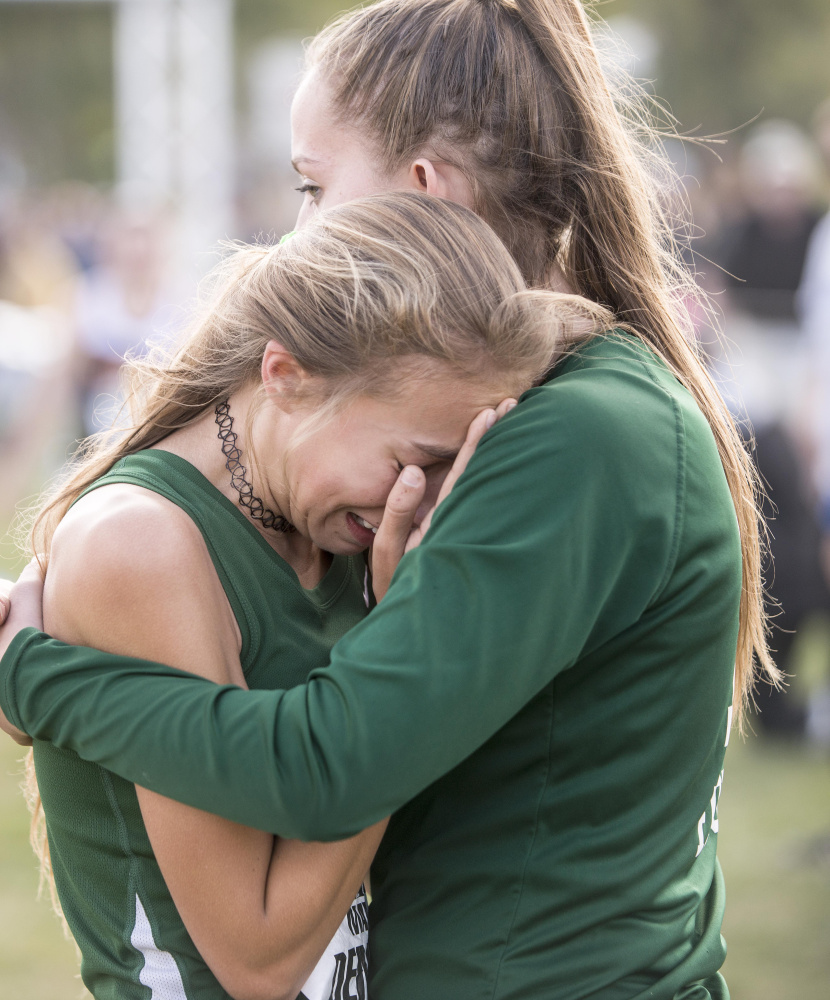 Winthrop's Maya Deming is comforted by a teammate at the finish line of the Festival of Champions on Saturday in Belfast.
