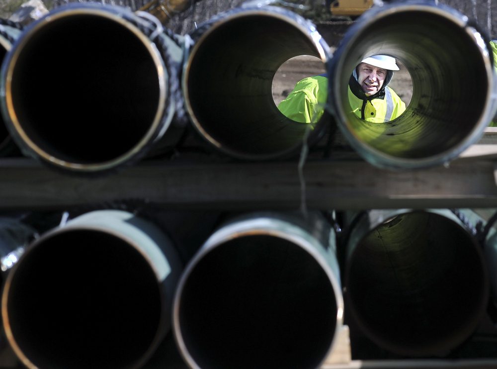 A worker inspects natural gas pipeline to be installed in the Kennebec County town of Windsor. Gas prices soared in the frigid winter of 2012-13, leading to calls for pipeline expansion.