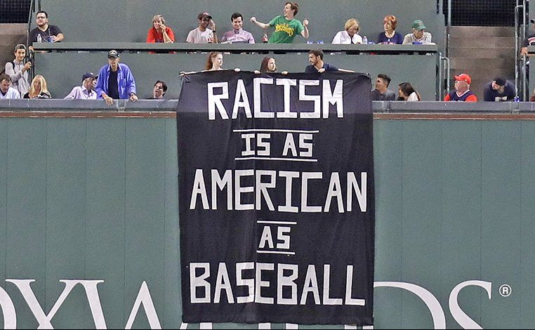 A banner is unfurled over the left field wall during the fourth inning of Wednesday night's game at Fenway Park.
