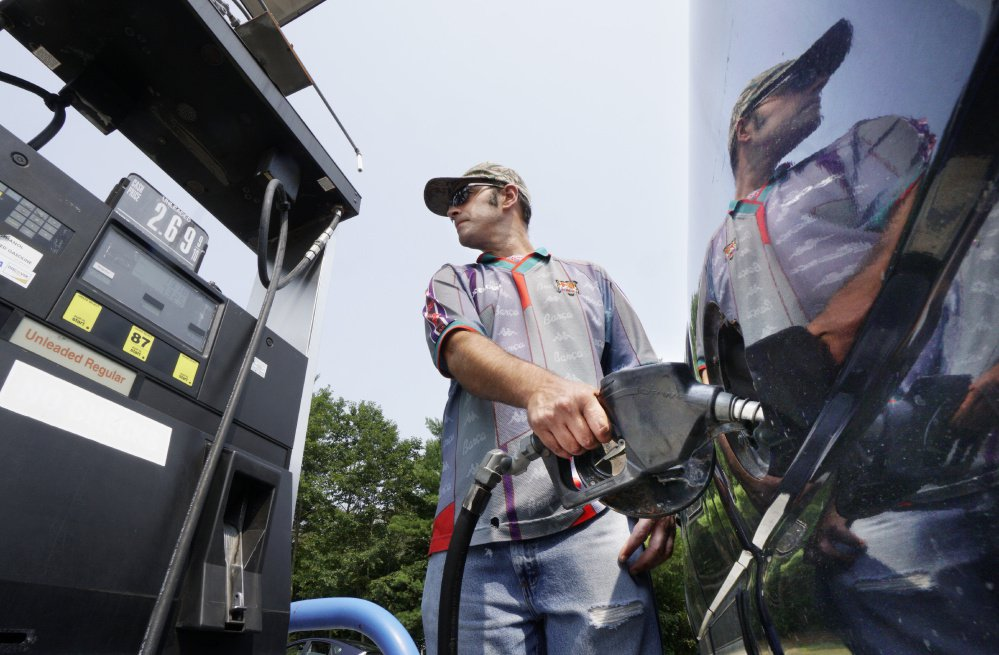 File photo: As his image reflects on the side of a pickup truck, attendant Matthew Legere pumps gas for a customer Tuesday at Rinaldi Energy in Saco. The full-service station's price of $2.69 for regular unleaded was slightly below the statewide average price of $2.71 for regular.