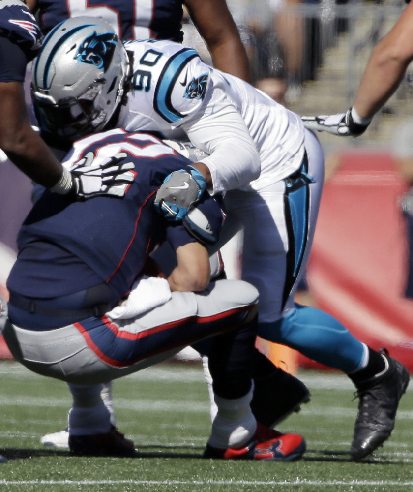 Carolina Panthers defensive end Julius Peppers sacks New England Patriots quarterback Tom Brady during the first half Sunday in Foxborough, Mass.