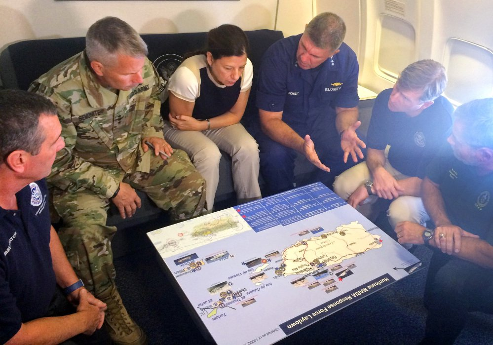 Acting Homeland Secretary Elaine Duke, center, is briefed on the Hurricane Maria response during a flight to Puerto Rico on Friday. President Trump on Thursday cleared the way for more supplies to head to Puerto Rico by waiving restrictions on foreign ships delivering cargo to the island.