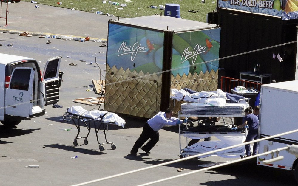 Investigators load bodies from the scene of the mass shooting at a music festival near the Mandalay Bay resort and casino on the Las Vegas Strip on Monday.