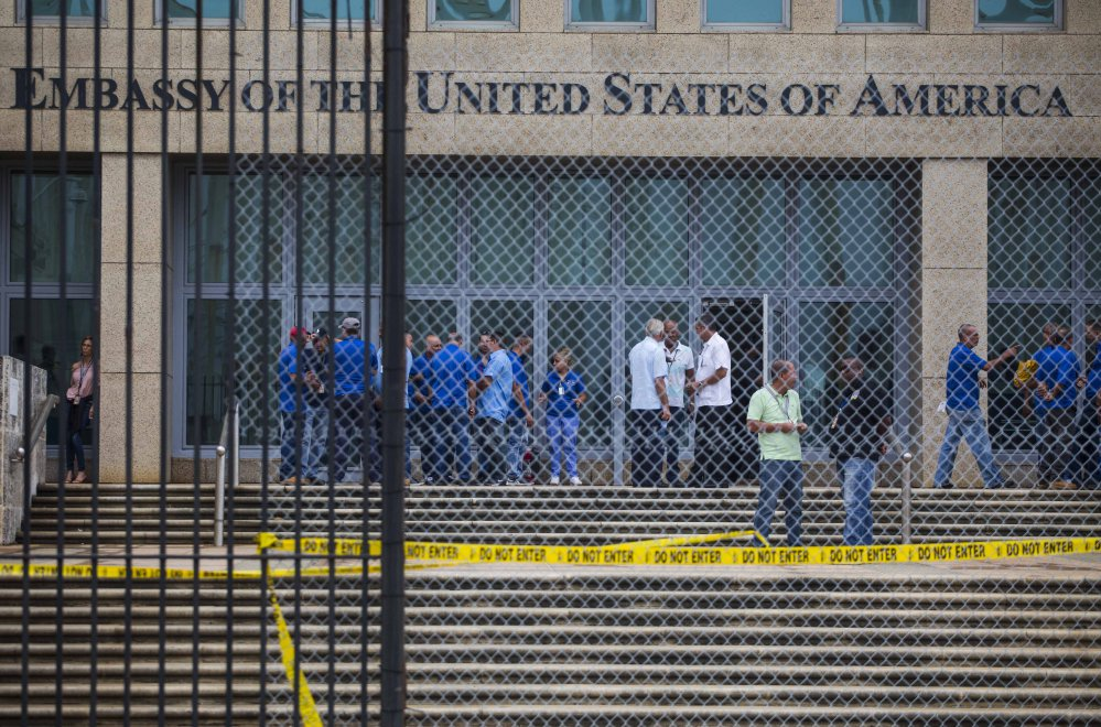 Staff members stand in the U.S. embassy facility in Havana, Cuba. At least 21 Americans in Cuba have been harmed by strange attacks over the last year.  (AP Photo/Desmond Boylan, File)