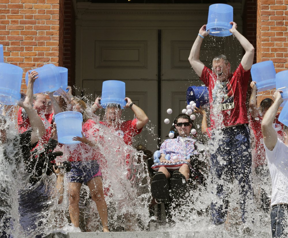 Pete Frates, seated at center in this 2015 photo, helped popularize the ice bucket challenge, which raised roughly $220 million in 2014. The ALS Association received $115 million of that and committed $89 million to research the disease.