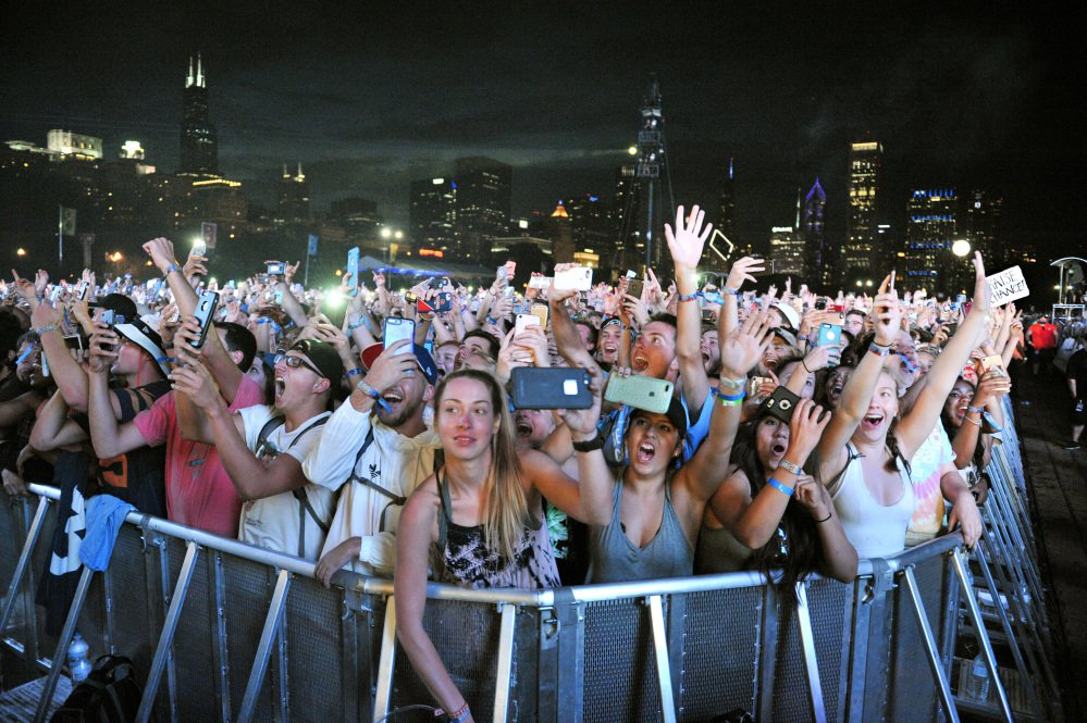 People enjoy the music at the Lollapalooza music festival Aug. 5 in Chicago. Stephen Paddock booked a room at a hotel that overlooks the park where the festival was held. On Sunday, he opened fire on a country music festival from his 32nd-floor hotel room in Las Vegas.