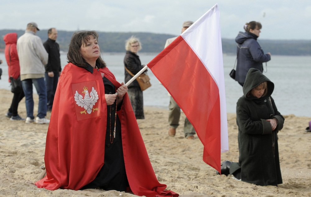 A worshipper holds a Polish national flag during a rosary prayer in Gdansk, Poland, Saturday. Hundreds of thousands of Polish Catholic faithful prayed the rosary around Poland's borders.