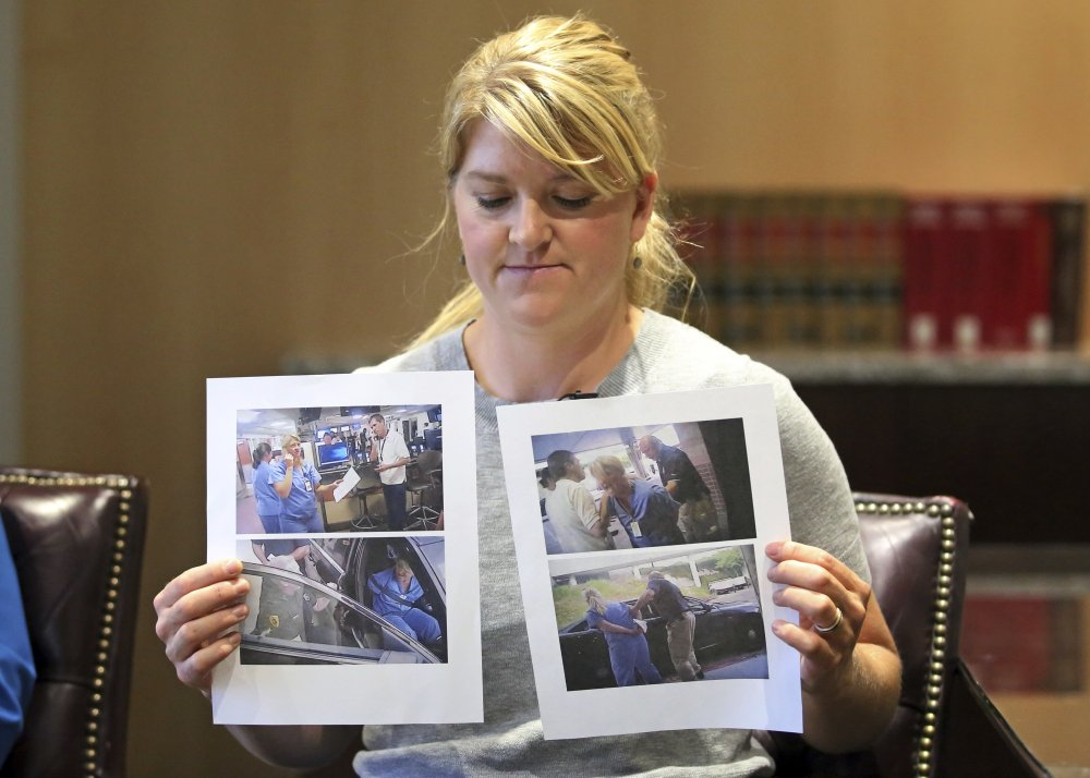 FILE - In this Sept. 1, 2017, file photo, nurse Alex Wubbels displays video frame grabs from Salt Lake City Police Department body cams of herself being taken into custody, during an interview in Salt Lake City. Authorities say a Utah police officer who was caught on video roughly handcuffing a nurse because she refused to allow a blood draw has been fired. (AP Photo/Rick Bowmer, File)