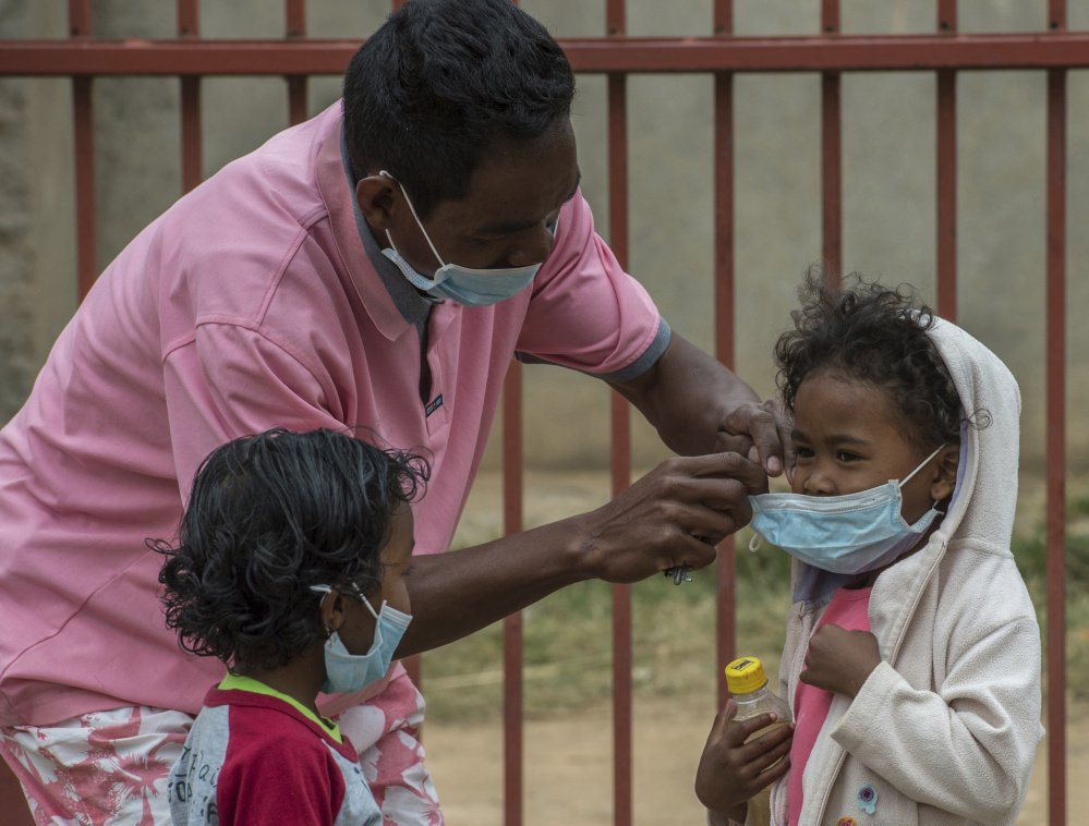 Face masks are placed on children in Antananarivo, Madagascar.  Authorities in Madagascar are struggling to contain an outbreak of plague that has killed dozens.