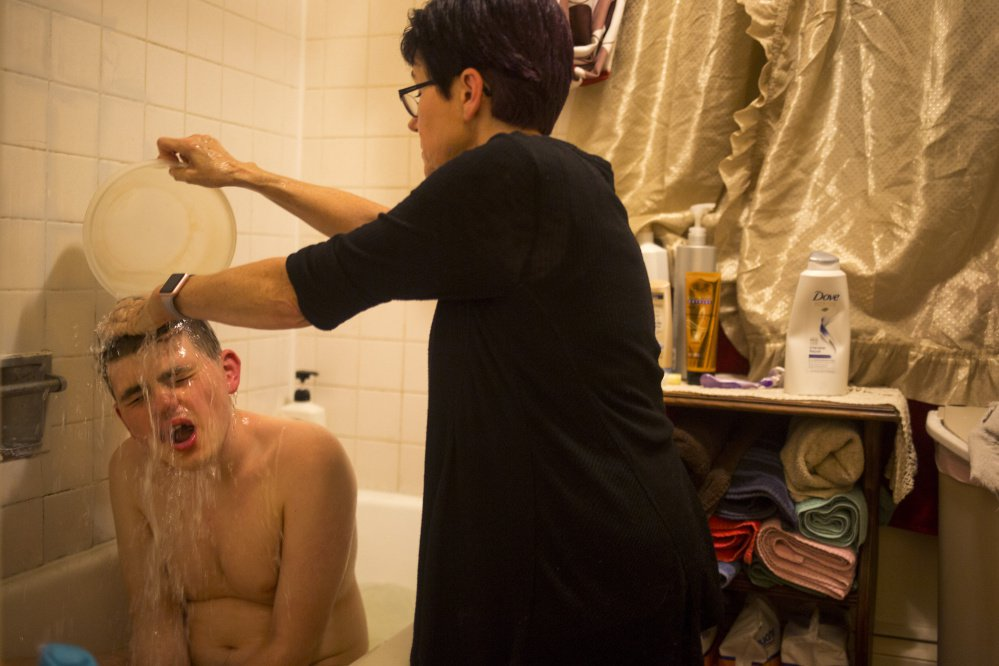 Donna Wall gives her son Christopher a bath Thursday. Because Wall lacks insurance coverage and is five years shy of Medicare eligibility, she can't afford doctor visits. Last year, she had soreness after falling on her tailbone, but she fears the day when she suffers an even more serious injury. Staff photo by Brianna Soukup