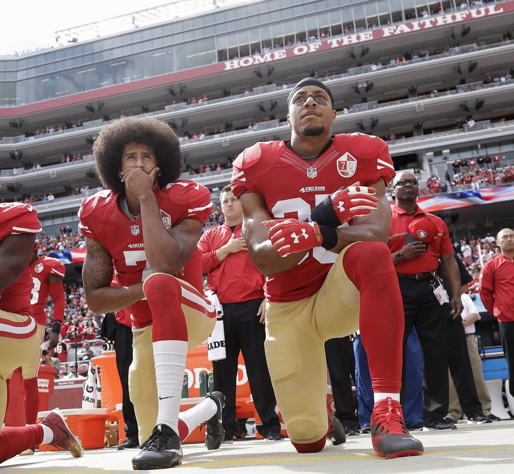 San Francisco quarterback Colin Kaepernick, and safety Eric Reid kneel during the national anthem before an NFL game against Dallas in 2016.  Kaepernick has filed a grievance with the league accusing teams of colluding to not hire him.