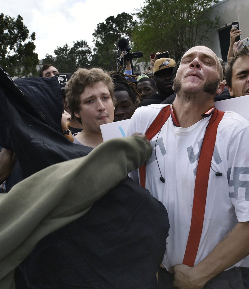 Randy Furniss, left, of Idaho recoils after getting punched in the face as he walks through a crowd of protesters outside a University of Florida auditorium where white nationalist Richard Spencer was preparing to speak Thursday. A supporter of Spencer, right, grabs a protester's tie as opposing groups confront each other.