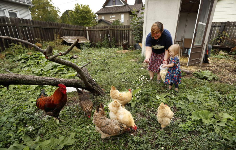 Tanya Keith of Des Moines, Iowa, and her daughter Iolana feed their chickens in the backyard of their home in Des Moines in September.