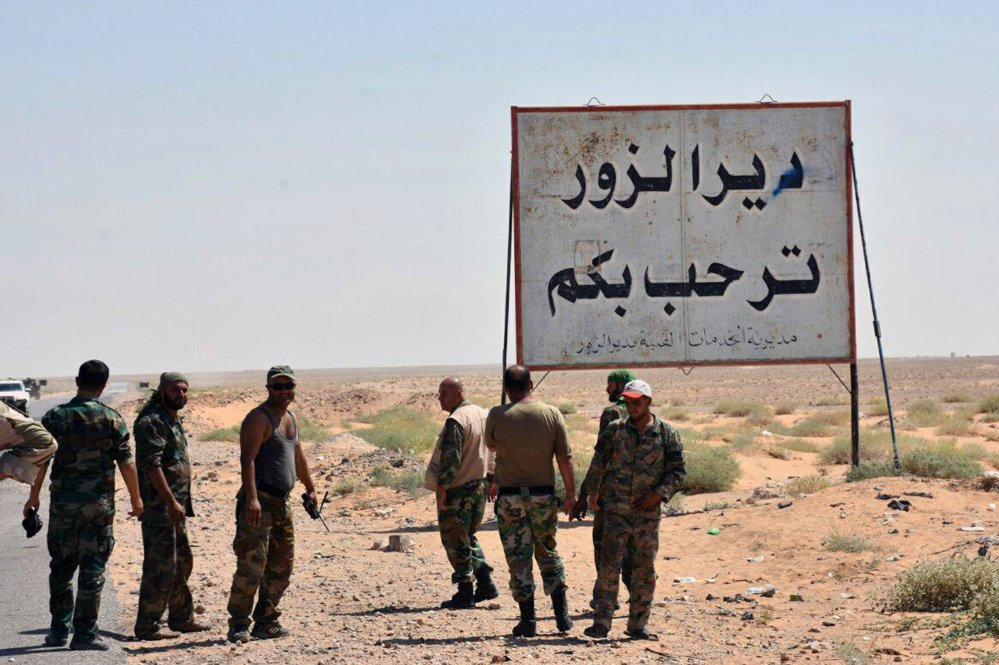 "A Sept. 3 photo shows Syrian troops and pro-government gunmen standing next to a placard in Arabic which reads ""Deir el-Zour welcomes you"" in the eastern city of Deir el-Zour, Syria. The oil-rich eastern Deir el-Zour province straddles the border with Iraq."