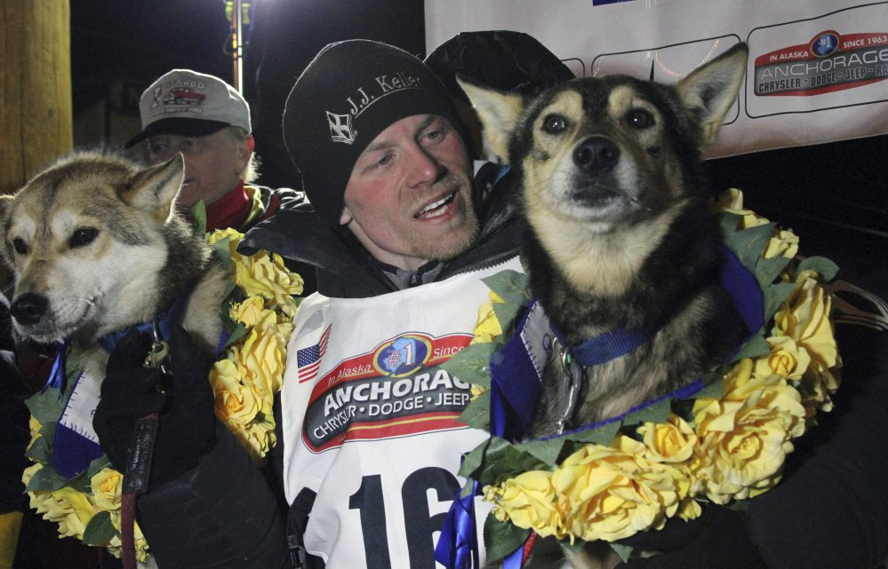 Dallas Seavey poses with his lead dogs Reef, left, and Tide after finishing the Iditarod Trail Sled Dog Race in Nome, Alaska. The four-time champion denies he administered banned drugs to his dogs in this year's race, and has withdrawn from the 2018 race in protest.