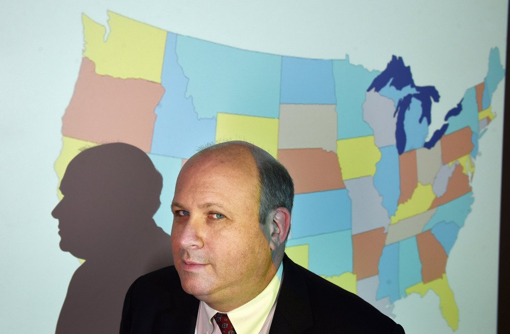 Marc Elias of Perkins Coie poses for a portrait in front of a projected map of the United States at the Washington firm in April 2016.