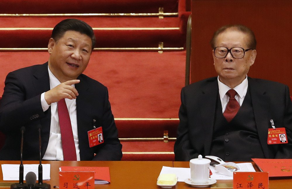 Chinese President Xi Jinping, left, chats with former President Jiang Zemin on Tuesday during the closing ceremony for the 19th Party Congress at the Great Hall of the People in Beijing. Despite his new status as China's most powerful ruler in decades, Xi lacks the broad popular support of the Chinese public, an analyst says.