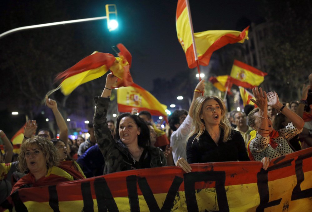 Anti-independence marchers wave Spanish flags as they protest the unilateral declaration of independence approved earlier by the Catalan parliament in Barcelona on Friday.