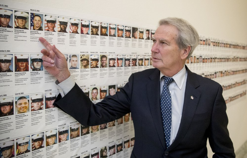 Rep. Walter Jones, R-N.C., points at a photo of Marine Sgt. Michael Edward Bits, the first military funeral he and his wife attended, and one of the many pictures of fallen soldiers along a hall leading to his office on Capitol Hill.