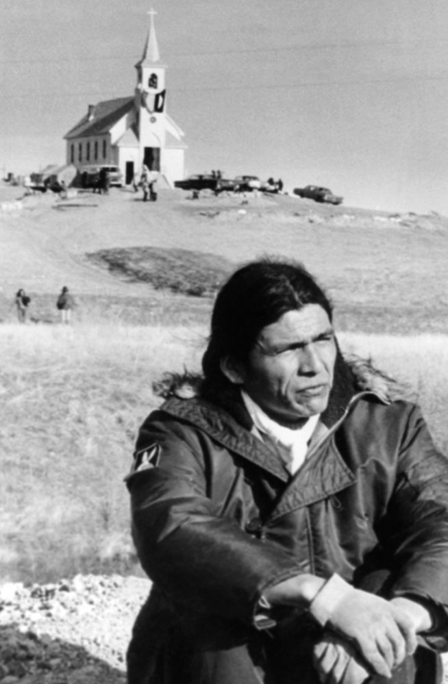 Dennis Banks sits in the open prairie on March 4, 1973, at Wounded Knee, S.D., where he led a protest against both the U.S. and tribal governments.