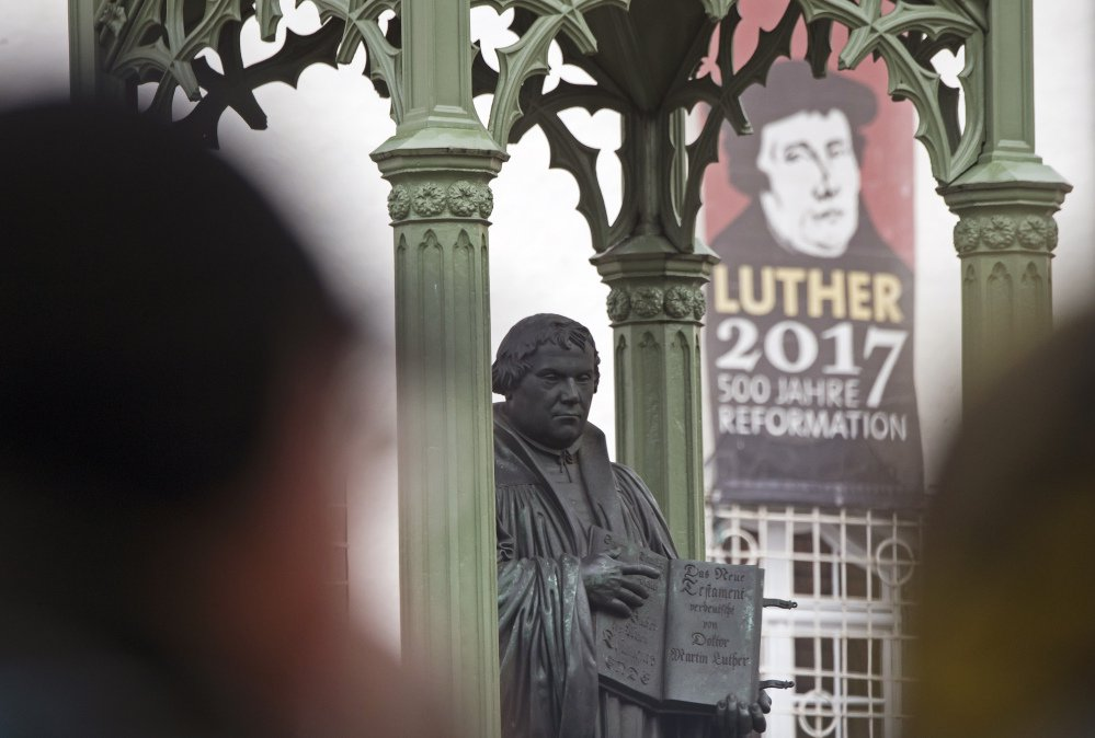 Visitors walk in front of the Martin Luther monument prior to celebrations marking the 500th Anniversary of the Reformation in Wittenberg, Germany, on Tuesday.