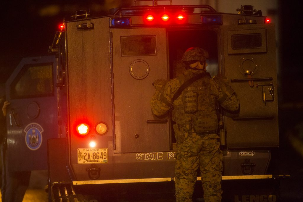 A swat team officer works outside a Maine State Police armored truck during Monday's standoff at the Motel 6 on Riverside Street in Portland.