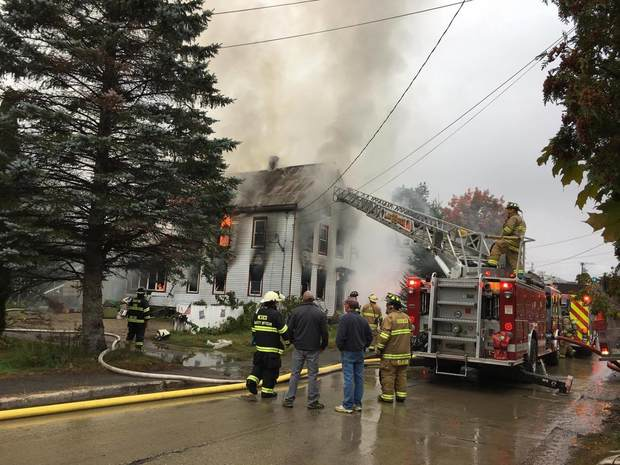Smoke pours from the home of Sue Mills at 34 Third St. in Dixfield on Monday. Firefighters from Dixfield, Rumford, Mexico and Peru worked for hours to extinguish flames. The cause is under investigation.