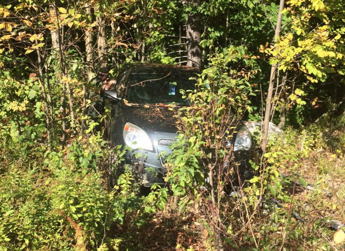 Clement Thibodeau's vehicle, discovered Saturday, is seen among trees on a remote road in Hancock County. Remains of a human body, found nearby, are believed to be that of Thibodeau.