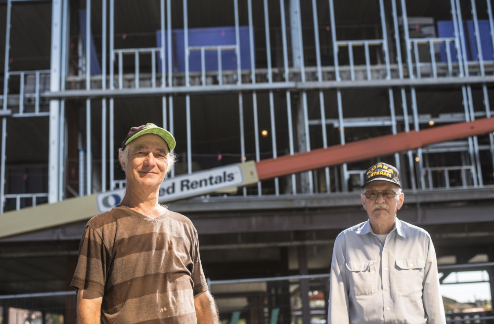 Raymond LaPointe, left, and Clifford Hebert, right, standing in front of the new Colby College building in downtown Waterville on Wednesday, have watched the building go up from the start and have gotten to know the construction workers in the process..