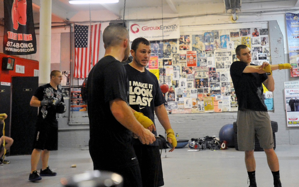 Joel Bishop, center facing, talks with friend Brandon Berry, left center, during a training session at the Portland Boxing Club in Portland on Oct. 1, 2014.