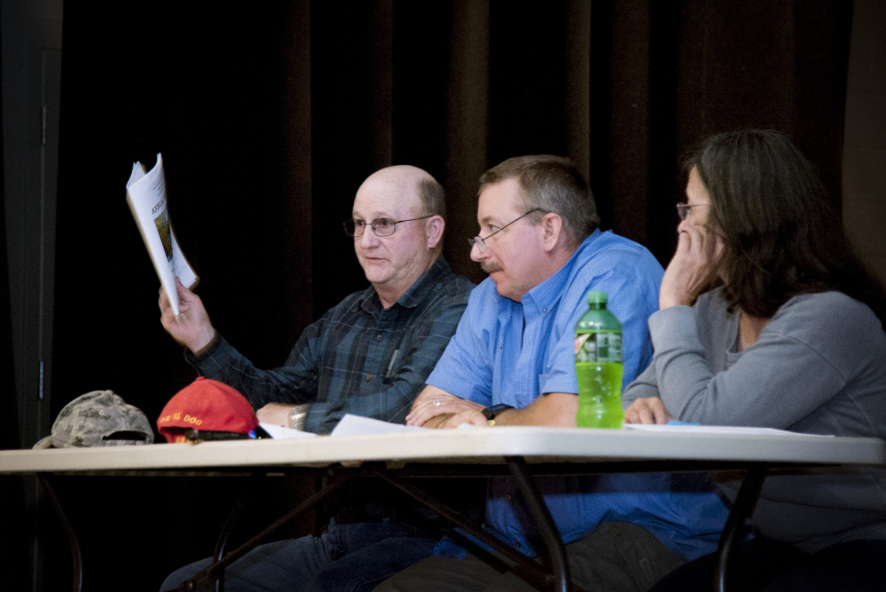 Farmingdale Selectman Wayne Kilgore, left, holds up the town warrant at the June Town Meeting, while Selectman James Grant and Selectwoman Nancy Frost watch the proceedings. Voters approved money to build a new fire station at the meeting, a project that Kilgore and others are working to complete.