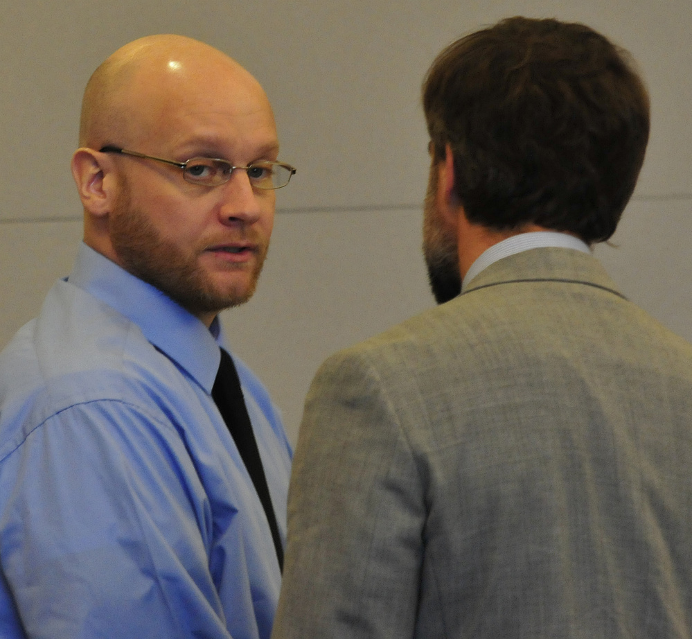 Murder defendant Robert Burton, left, speaks with attorney Hunter Tzovarras on Monday during his trial at the Penobscot Judicial Center in Bangor before taking the stand in his own defense.