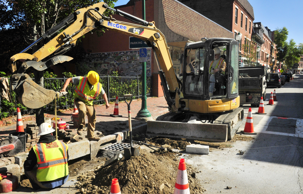 A crew from Steven A. McGee Construction installs a new granite curb Tuesday on Water Street in Gardiner.